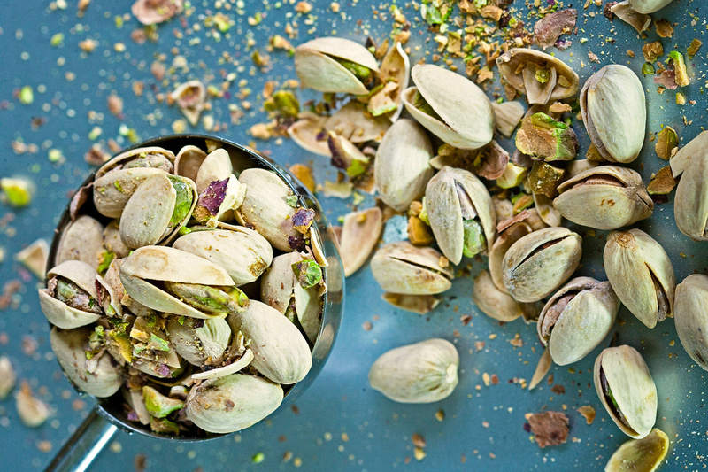 Food Photography Portfolio - Spoon containing pistachios with shelled nuts scattered on a blue-grey background. © bokeh photographic (Alistair Grant): Food Photographer, St Ives, Cambridge.