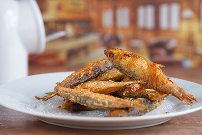 Food Photography Portfolio – Beer Battered Sardines piled on plate. © bokeh photographic (Alistair Grant): Food Photographer, St Ives, Cambridge.