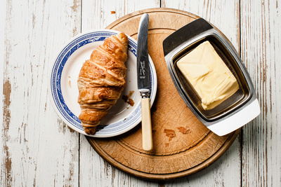 Food & Drink Photography Image of Croissant on a blue rimmed plate with butter tray on a round wooden bread board. © bokeh photographic (Alistair Grant): Food Photographer, St Ives, Cambridge.