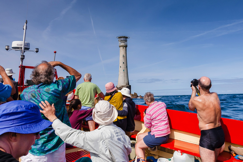 Freelance Photographer Cambridge Blog Image | Blog 48 | Favouritism (A guy wearing only swimming trunks stands out on a boat full of people photographing the iconic Bishop Rock Lighthouse off the Isles of Scilly). © bokeh photographic (Alistair Grant): Freelance Photographer; Food & Drink Photographer; Commercial Photographer, Product Photographer & Packshot Photographer; Event Photographer; Portrait Photographer; Corporate Photographer & PR Photographer; Engagement Photographer & Wedding Photographer and Photography Training Courses, St Ives, Cambridge.